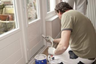 painter white washes an exterior door